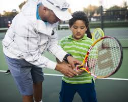 Valter Tennis Lesson Pic with Student Holding Tennis Racket